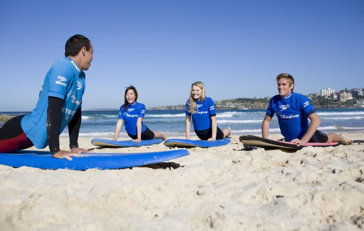 Two young women and a young man learning to surf with a 'Let's Go Surfing' instructor at Bondi Beach